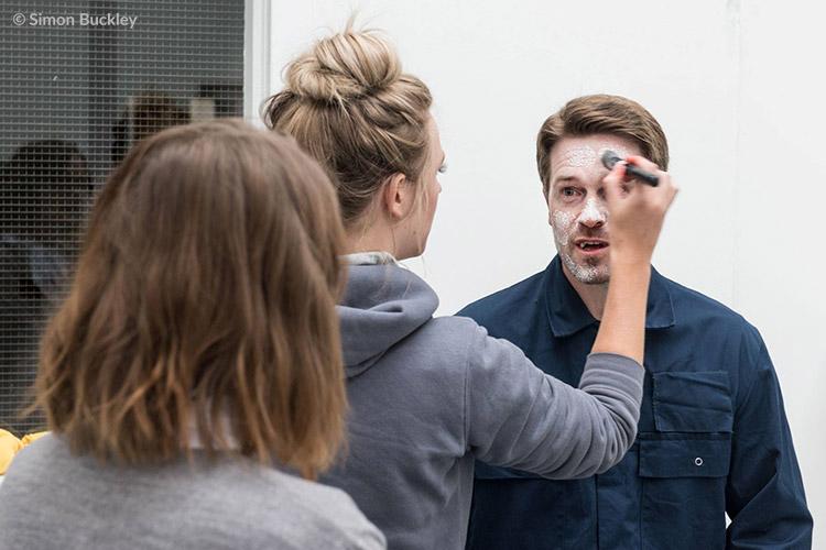 Make-up artist Charlotte Maclaine turning Garth Maunders into Dredvoka while Lauren Ashley Carter looks on.
